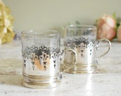Pair of vintage drinking glasses or tumblers with silver plated holders and handles.