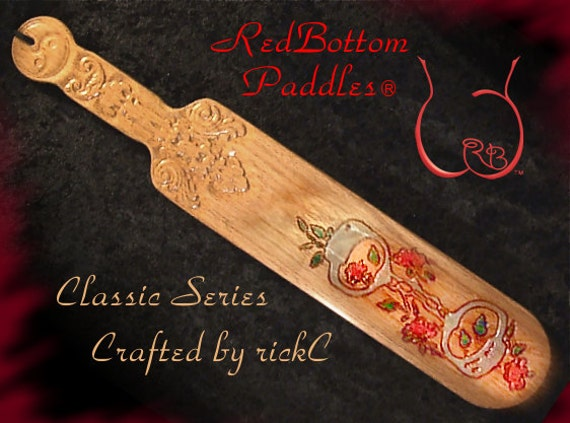 Paddle with Cuffs & Roses art engraved on front, handle carved both sides. INCLUDED: Black leather look pouch offering class and protection