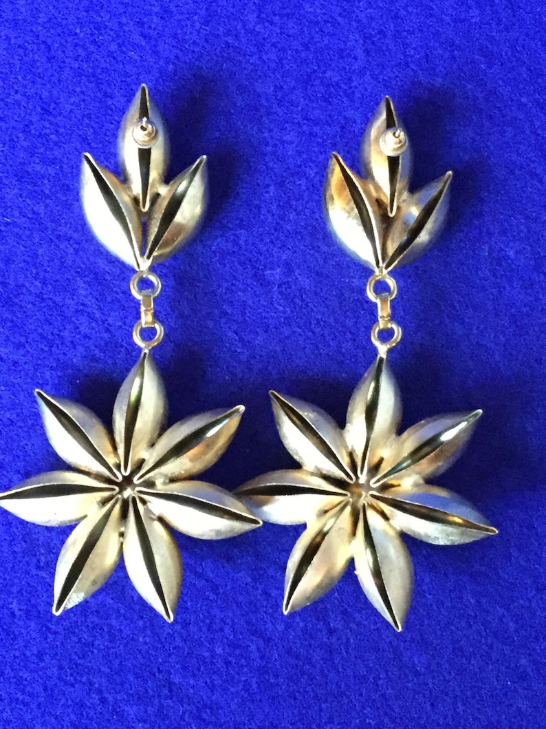 Vintage 1970s chandelier drop earrings in gold toned metal with dramatic plastic faux rhinestone centres.