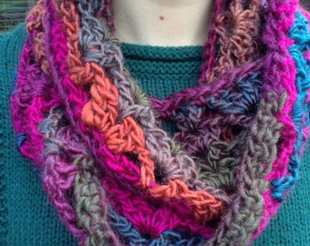 Hand-crocheted chunky cowl / infinity scarf, multi-tonal jewel colours of pink, bronze, and blue, and detachable button brooch