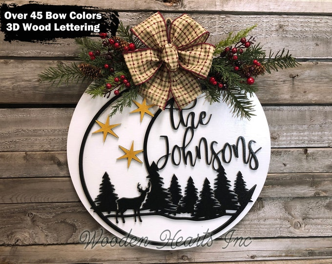 """Christmas Sign for Front Door PERSONALIZED Holiday Hanger Wreath Wood Round Moon Deer Trees Greenery Berries, 16"""" 3D Wood Lettering Xmas Bow"""