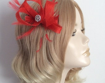 A RED FASCINATOR, Made of Sinamay, with stripped hackle feathers, Crystal and pearl, on a clip