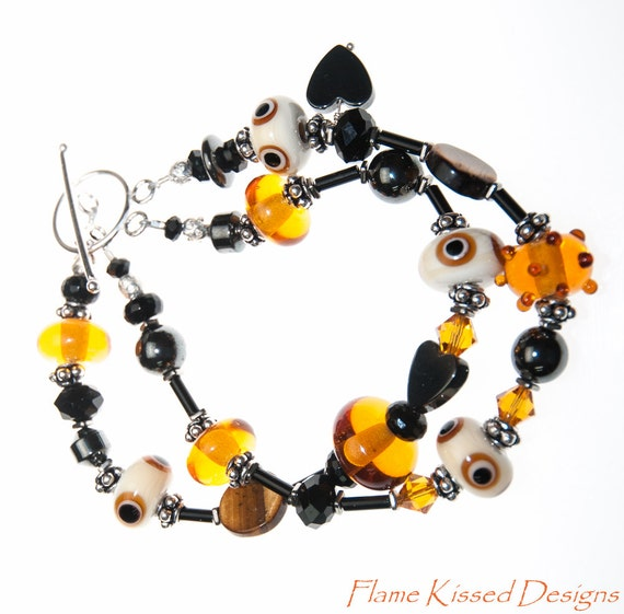 The EYES HAVE IT! A beautiful double strand handcrafted lampwork bead bracelet featuring earthtones that are brought to life.