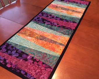 Modern quilted batik table runner, jewel tones, purple green gold, reversible with brown and gold batik on back. Use as wall hanging too.