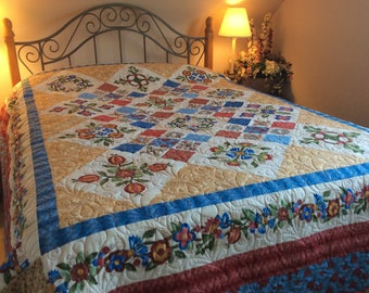 Queen size bed quilt, Jacobean style floral prints in red, cobalt blue and gold with  green brown leaves.  Rose of Sharon style flowers