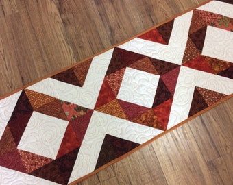 Traditional quilted diamond pattern table runner in bronze, gold and oranges with white background. Thanksgiving coffee table runner