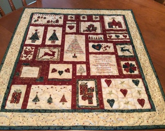Quilted Christmas wall hanging, table topper in red green cream and quilted with gold thread in star pattern. Xmas trees reindeer and hearts
