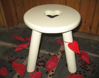Hand crafted thick top wooden milking stool with a red heart