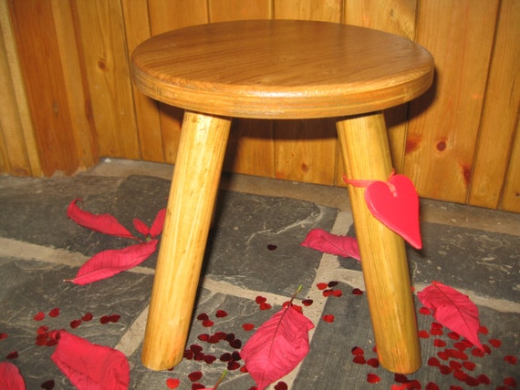 Lighter coloured Oak topped wooden milking stool with a red heart
