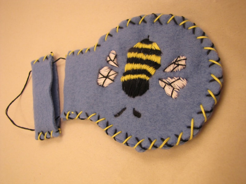 Mongolian needle pouch constructed from blue felt with decorative embroidered bumblebee