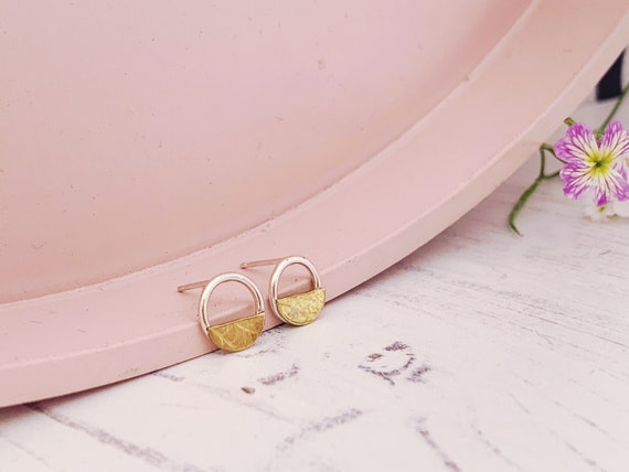 Minimal circle and half-moon studs made with recycled sterling silver and brass. petal/leaf pattern.