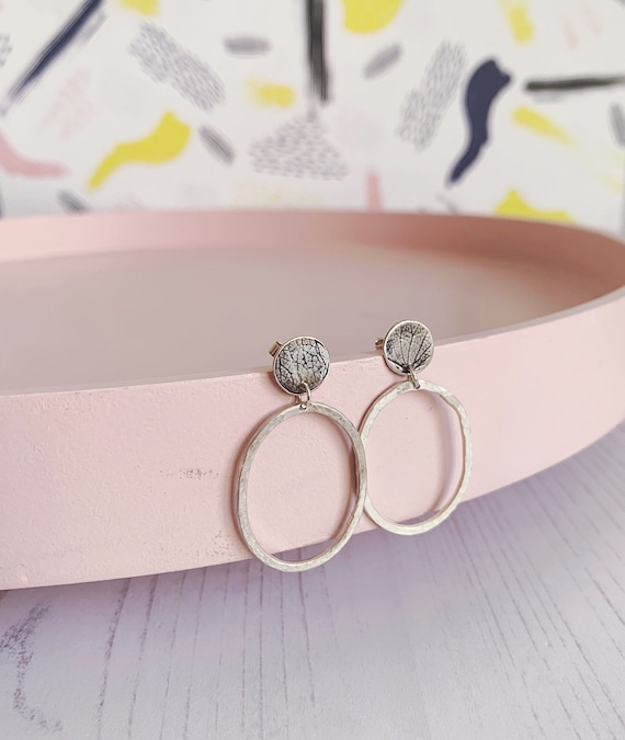 Silver dangly oval hoops, studs with hydrangea petal leave pattern, made using recycled eco sterling silver.