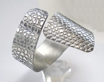 Open  bracelet cuff in aluminum with snakeskin finish, with personalized text.