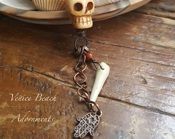 hand carved bone skull with copper chain and bead accents on brown leather cord