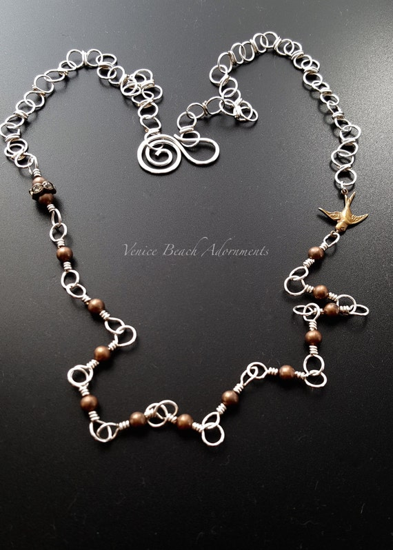 Layering necklace. Silver and copper beaded handmade chain necklace with bird charm
