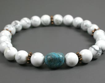 White howlite stacking stretch bracelet with a turquoise dyed quartzite focal and antiqued copper plated roundels