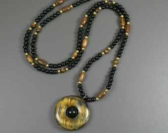 Tiger eye donut pendant with rainbow obsidian center on beaded strand of obsidian, wood, tiger eye, and gold plated beads
