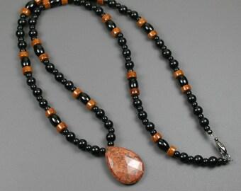 Faceted burnt orange feldspar teardrop pendant on beaded strand of brown riverstone, black onyx and obsidian