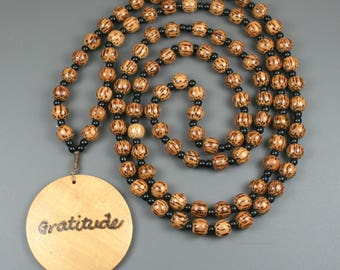Coconut palm tree wood gratitude beads with obsidian and a round wooden focal engraved with the word gratitude