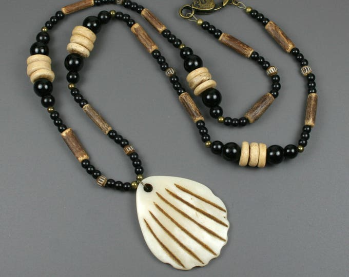 Shell pendant of carved bone on beaded strand of obsidian, coconut wood, coconut shell, antiqued bone, and antiqued brass