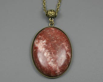 Dark red banded stone cabochon in an antiqued brass bezel with antiqued brass bail and chain