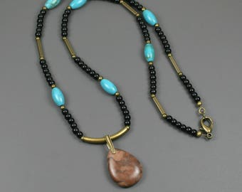 Bronze zebra jasper pendant on strand of obsidian, turquoise magnesite, and antiqued brass