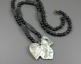 Lip shell leaf pendant on strand of black wood, blackstone, and gunmetal beads