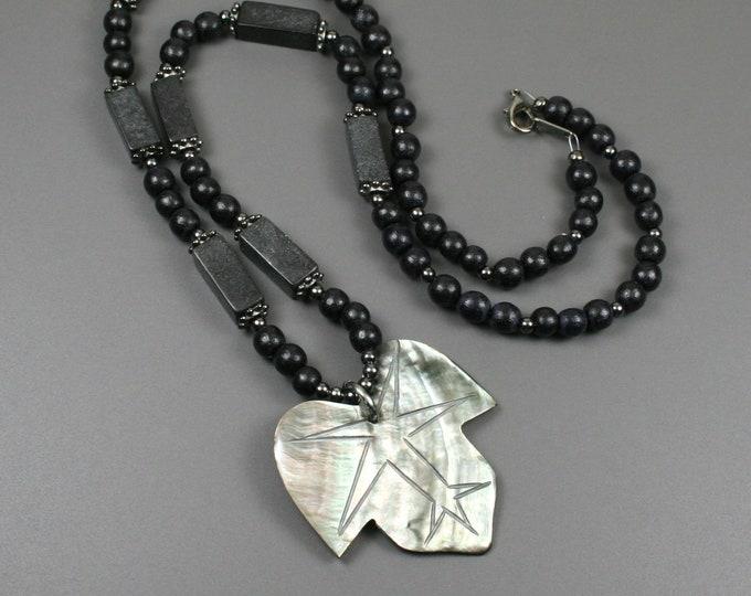 Lip shell leaf pendant on strand of black wood, blackstone, and gunmetal beads