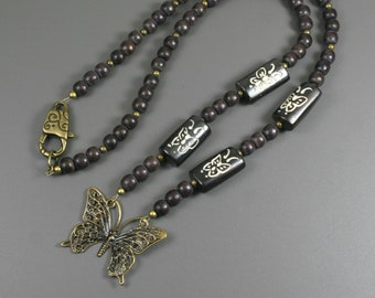 Antiqued brass butterfly pendant with dark brown wood, carved bone butterfly beads, and antiqued brass accents