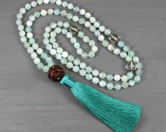 Faceted sea foam green agate and crystal quartz hand knotted mala in the Tibetan style with a carved sandalwood guru bead and silk tassel