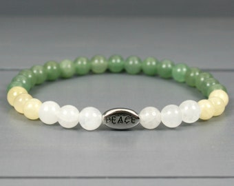 Green aventurine, yellow calcite, and snow quartz stacking stretch bracelet with an antiqued rhodium plated pewter PEACE bead