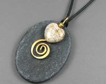 Black slate oval pendant with stone heart and gold spiral decoration on black cotton cord
