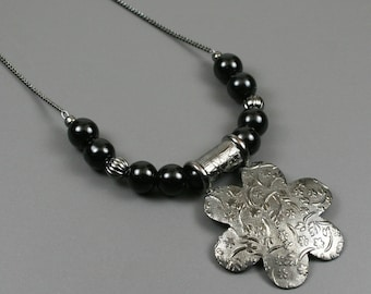 Texturized gunmetal plated flower pendant flanked by obsidian beads and fluted gunmetal accents on gunmetal chain