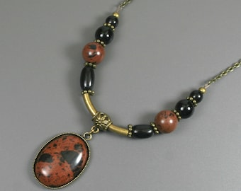 Mahogany obsidian cabochon in an antiqued brass bezel cup with antiqued brass and obsidian accents on antiqued brass chain