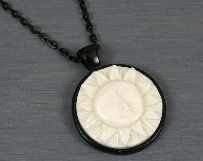 Sun face with open eyes bone cabochon pendant in black bezel setting on black chain