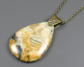 Yellow crazy lace agate teardrop pendant on antiqued brass chain