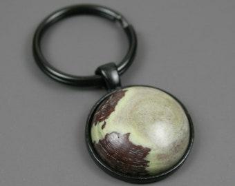 Green stone key chain in a black bezel setting, black key ring, green key chain, stone keychain