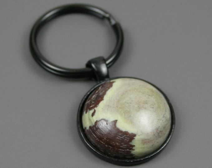 Green stone key chain in a black bezel setting