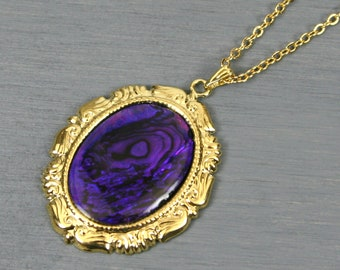 Purple paua shell pendant set in a gold plated setting on gold plated cable chain