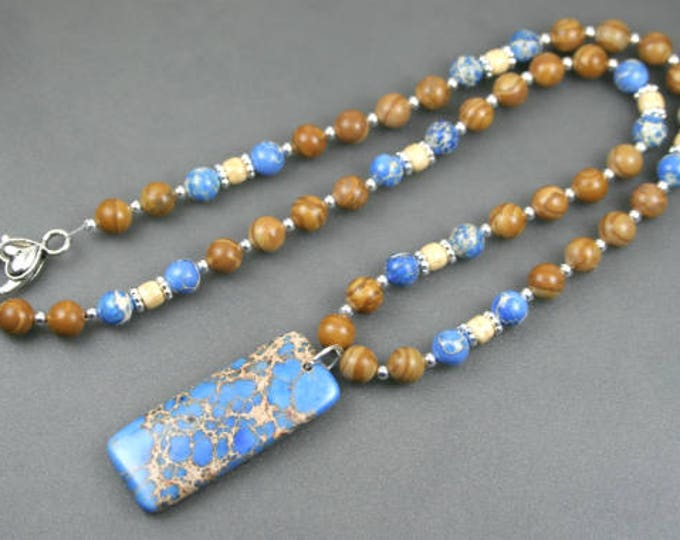 Blue magnesite pendant on beaded strand of tiger jasper, blue magnesite, antiqued bone, and silver plated beads