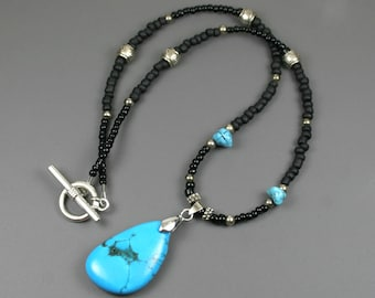 Turquoise magnesite pendant on beaded strand of black, turquoise, and silver beads