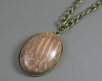 Banded brown stone cabochon in an antiqued brass bezel on antiqued brass chain