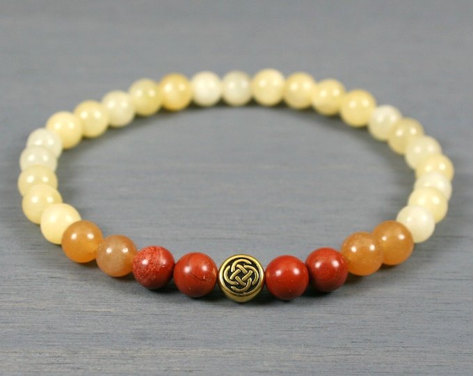 Red jasper, red aventurine, and yellow calcite ombre stretch bracelet with an antiqued gold plated Celtic knot focal