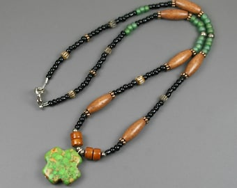Green magnesite Greek cross pendant on beaded strand with glass, wood, bone, and metal beads