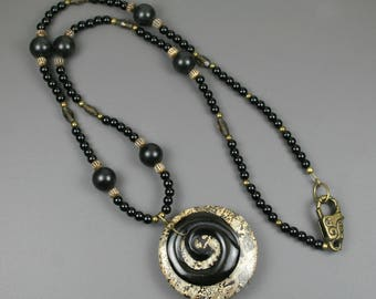 Black horn spiral on brown jasper stone pendant on strand of obsidian, antiqued bone, smoky quartz, and antiqued brass