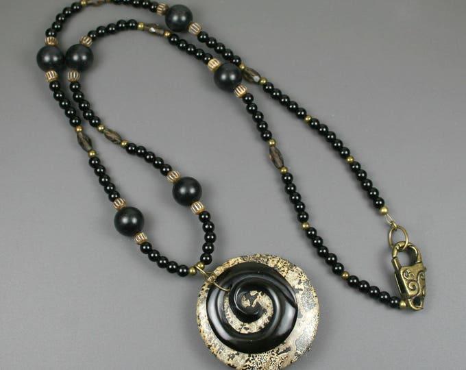Black horn spiral on brown jasper stone pendant on strand of obsidian, antiqued bone, smoky quartz, and antiqued brass