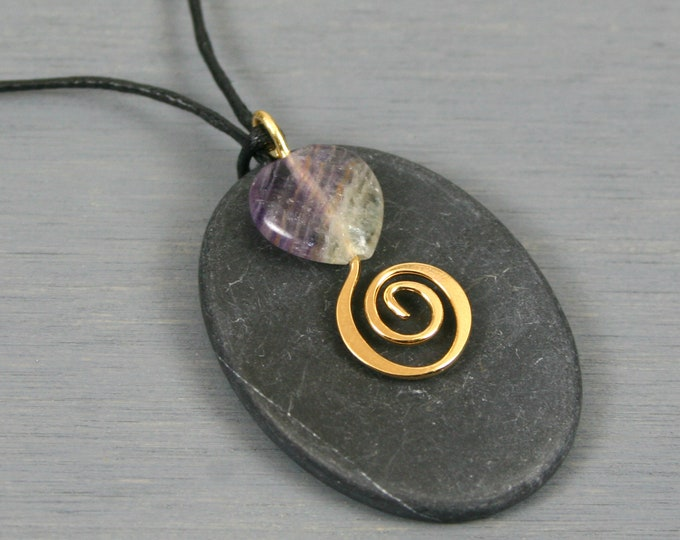 Black slate oval pendant with fluorite heart and gold spiral decoration on black cotton cord