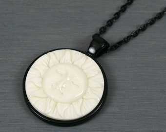 Sun face with closed eyes bone cabochon pendant in black bezel setting on black chain