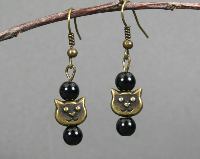 Obsidian and antiqued brass cat face earrings on bronze colored ear wires