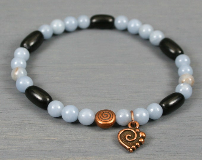 Blue angelite and black horn stacking stretch bracelet with an antiqued copper plated spiral focal bead and spiral heart charm